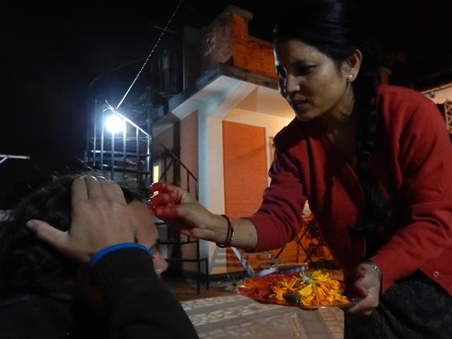 Rasini, l'épouse de Mahen, appose un tika sur le front lors de la cérémonie du Nouvel An Newar - 4 novembre 2013 (Crédit : Obee)
